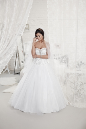 25 to 30: Beautiful bride standing in bedroom in wedding dress. Full size. Stock Photo