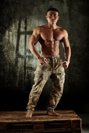 young asian: Male bodybuilder posing with bare chest in studio.