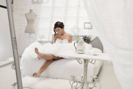woman in bed: Beautiful happy bride sitting on bed in white bedroom, smiling happy.