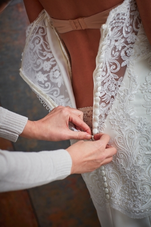 dressing up: Dressing up the bride on wedding-day. Photographed from behind. Stock Photo