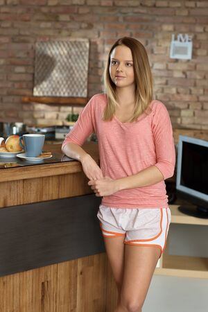 young woman smiling: Young woman in casual clothes standing at kitchen counter, looking away.