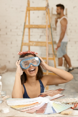 protective eyewear: Young woman laughing in protective eyewear at home renovation.