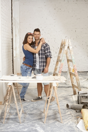 renovating: Happy young loving couple renovating home. Stock Photo