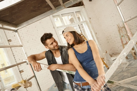 tinkering: Happy young loving couple standing at renovation site.