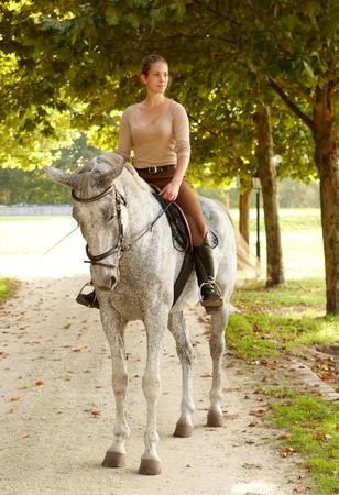 Jinete femenino en la montura del caballo hermoso en el verde.