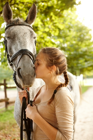 tenderly: Young female rider kissing horse tenderly.