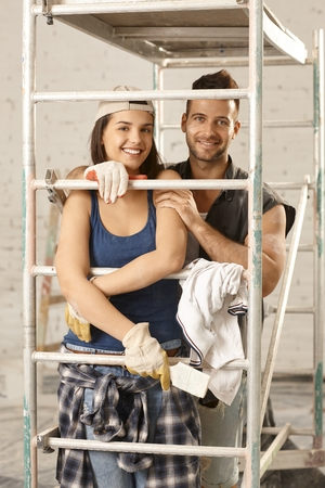 Loving couple renewing home, smiling happy, embracing under scaffold.