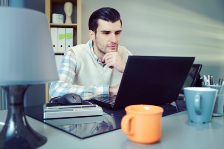 stockphoto: Portrait of young businessman sitting at desk, working with computer.