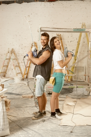 renovating: Happy young couple standing back-to-back, using power drill, renovating home, smiling, looking at camera.