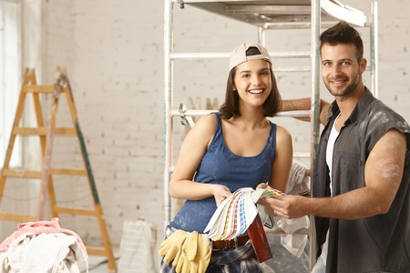 color scale: Happy young diy couple building new home, choosing paint colors, from color scale. Stock Photo