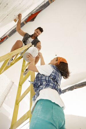 ladder: Young couple renovating home diy. Woman passing painting to man on top of ladder.