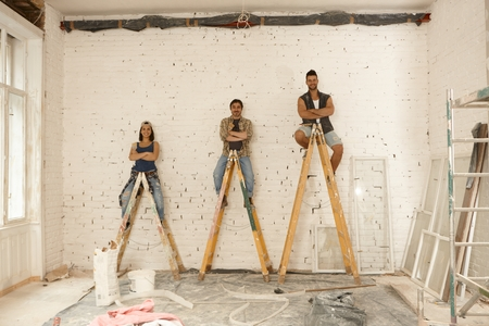 white color worker: Team photo of workers renovating house, sitting on top of ladder, smiling arms crossed.