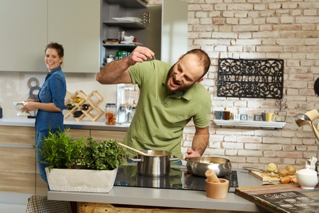 boyfriend: Young couple cooking together in kitchen, man tasting spaghetti. Stock Photo