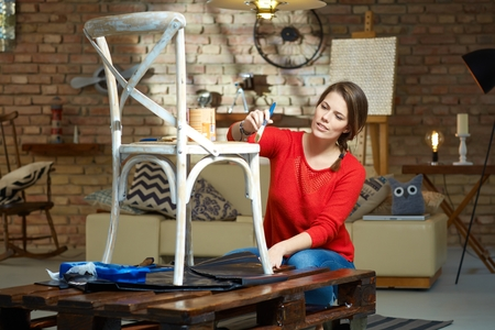 Diy woman painting, renewing chair at home. Stockfoto