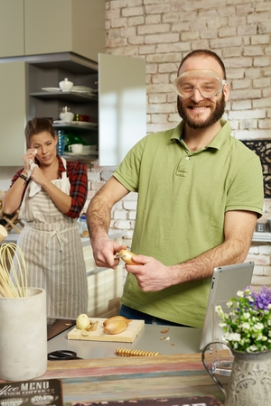 protective eyewear: Funny man peeling onion in protective eyewear in kitchen. Stock Photo