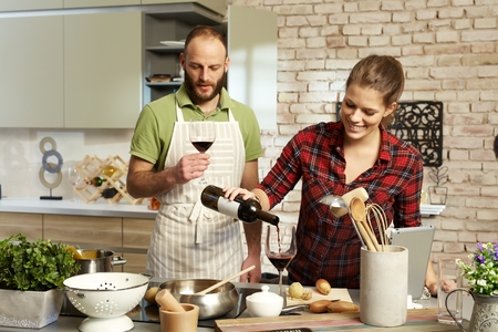 feliz pareja cocinar juntos en la cocina, beber vino tinto. Foto de archivo
