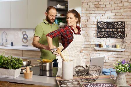 mandil: Pareja de cocina en la cocina, la mujer que pone el delantal, el hombre que anudar. Foto de archivo