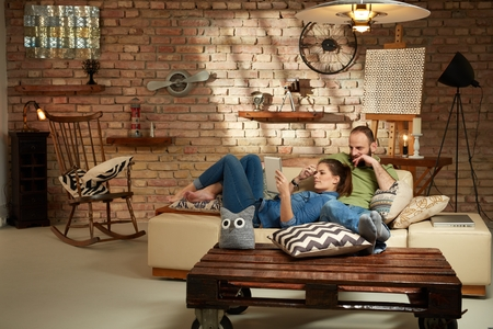 living style: Young couple relaxing at home, using tablet. Stock Photo