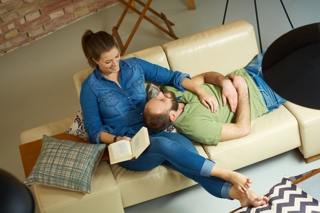 Loving couple resting on sofa at home. Photographed from above. Stock Photo