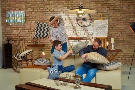 family fight: Happy family having pillow fight at home, having fun.