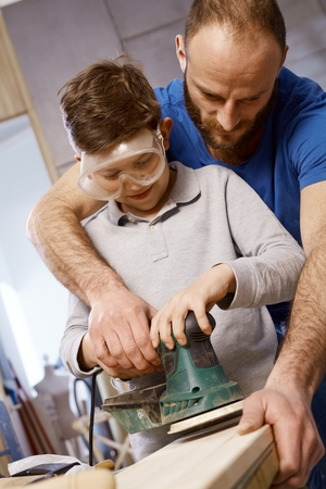 dad son: Closeup photo of diy father teaching son tinkering, using jig saw.