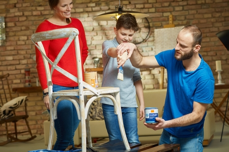 tinkering: Diy family renewing chair at home, father teaching son painting.