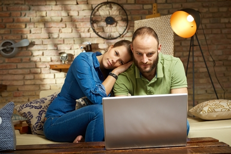 laptop home: Loving couple using laptop computer at home.