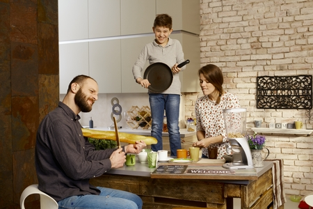 pretending: Family forming a band in kitchen, pretending to play on instruments.
