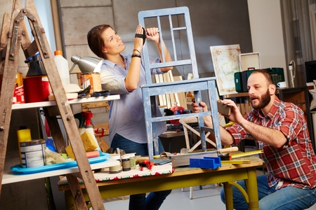Busy couple renewing chair in home workshop. Stockfoto