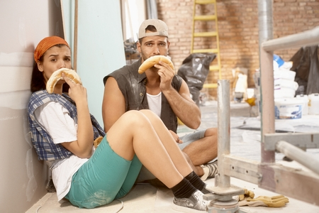 renovating: Young couple sitting on floor after daily work on renovating home, making sad face from crescent roll. Stock Photo