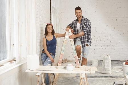 Felice giovane coppia sorridente, in piedi sulla scaletta a casa in costruzione.