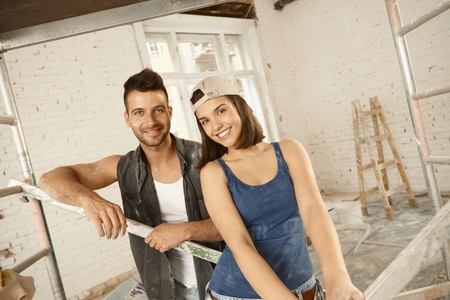 renovating: Portrait of young loving couple renovating home, smiling, looking at camera.