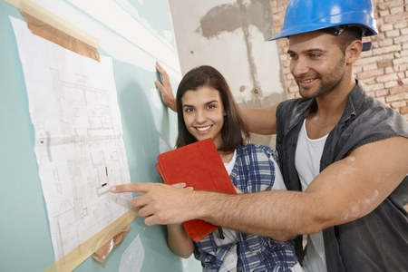 young guy: Young couple looking at floor plan at renovation site, smiling happy.