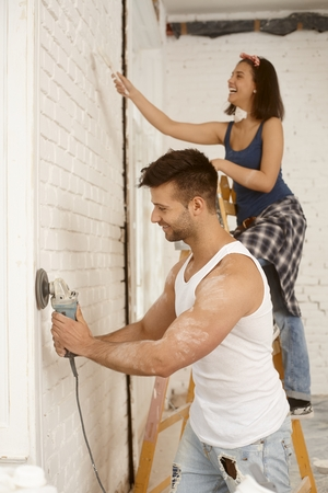 tinkering: Young couple renovating home.