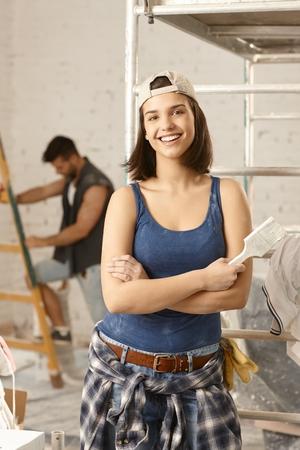 mujer sola: Mujer joven atractiva que la renovación de su casa, sonriendo feliz. Foto de archivo