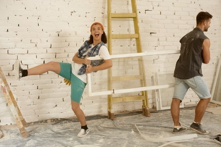 window frame: Happy young couple having fun at home renovation, holding window frame. Stock Photo