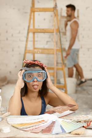 misbehaving: Playful woman sticking tongue, wearing protective eyewear at home renovation.