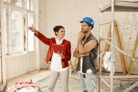 contractor: Female client and contractor talking at renovation site.