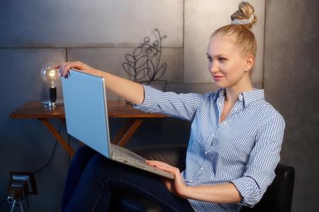 shutting: Young woman shutting down laptop computer. Side view. Stock Photo
