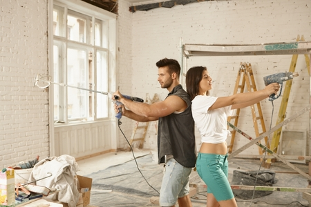 power drill: Young couple standing back-to-back, using power drill, renovating home.