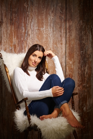 woman sweater: Attractive casual woman sitting in chair with pulled up legs, front of antique wooden wall.