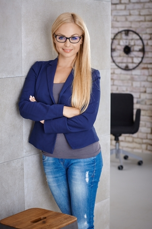 women in jeans: Confident young blonde woman standing against wall arms crossed, smiling happy, looking at camera. Stock Photo