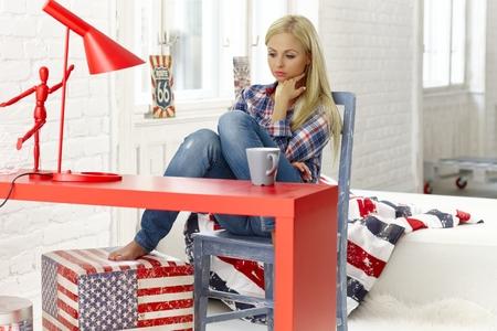 mujer sola: joven reflexiva sentado en el escritorio en casa en mal humor, mirando hacia abajo,