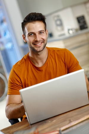 Handsome young man using laptop computer, smiling happy.