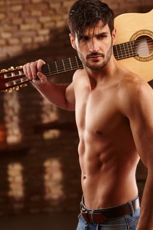 Sexy latin type man holding guitar in shoulder, bare upper body.