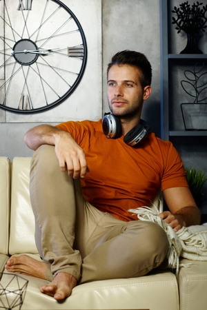 stockphoto: Young man sitting on sofa at home, daydreaming, looking away. Stock Photo