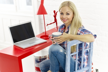 Casual young blonde woman sitting at desk at home, drinking tea, having laptop.
