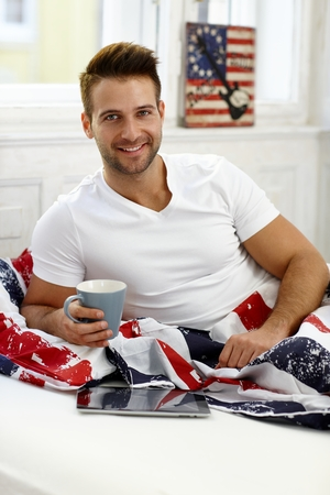 levantandose: Hombre joven feliz sonriendo en la cama por la mañana, la celebración de café, usando la computadora de la tableta. Foto de archivo