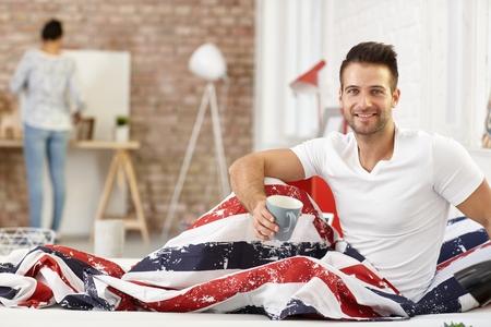 levantandose: Hombre joven feliz tomando un café por la mañana en la cama, sonriendo, mirando a la cámara.