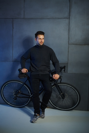 bristly: Young man waiting by wall, leaning against bicycle, looking away.